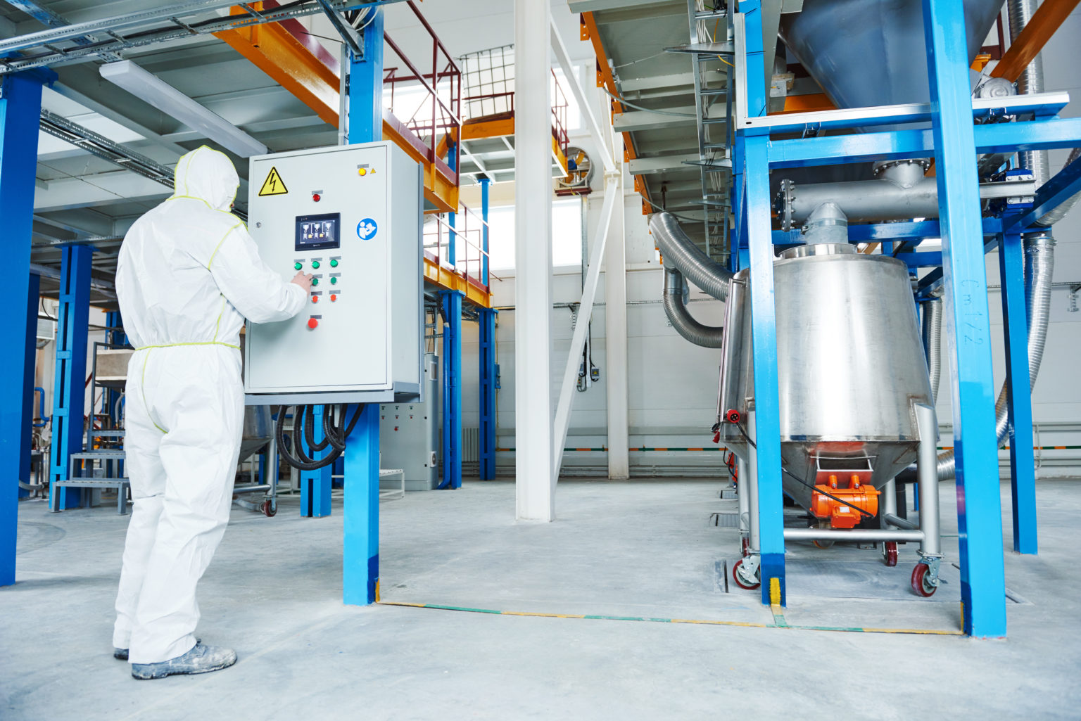 chemical industry worker operating equipment at technological industrial factory