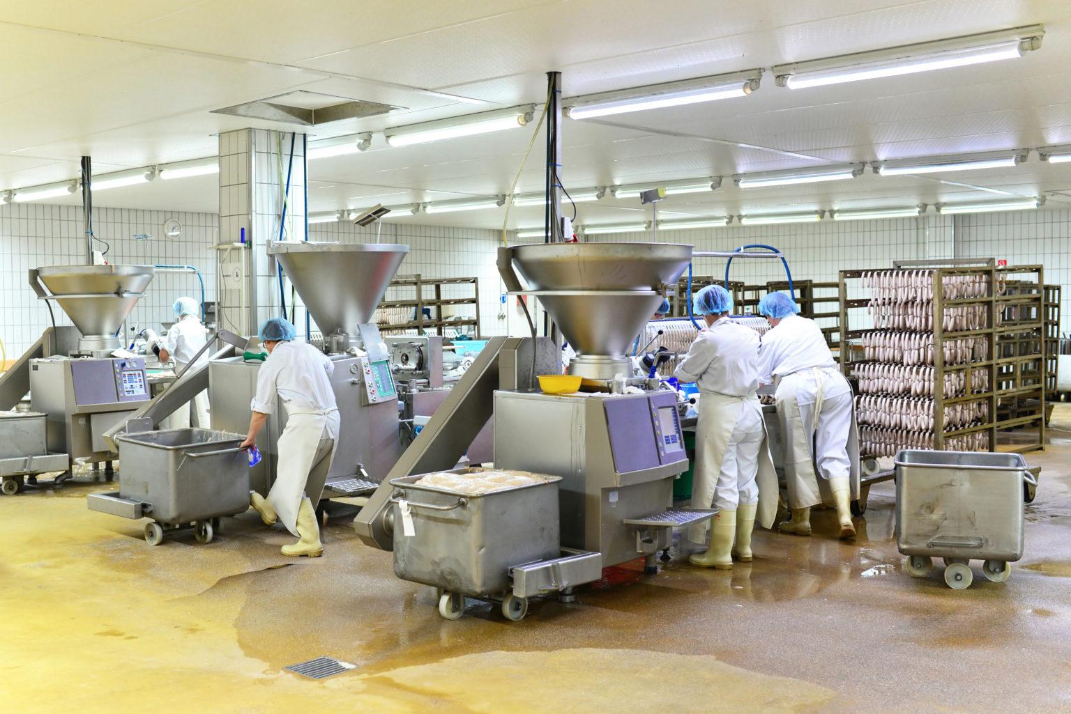 Arbeiter in einer Fleischerei bei der Herstellung von Würsten // Workers in a butcher's shop producing sausages